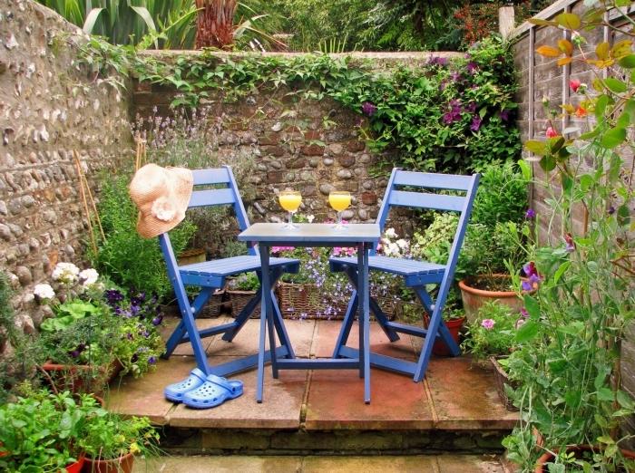 comment décorer un petit jardin avec terrasse et fleurs, mobilier de jardin à design pliant de couleur bleu foncé
