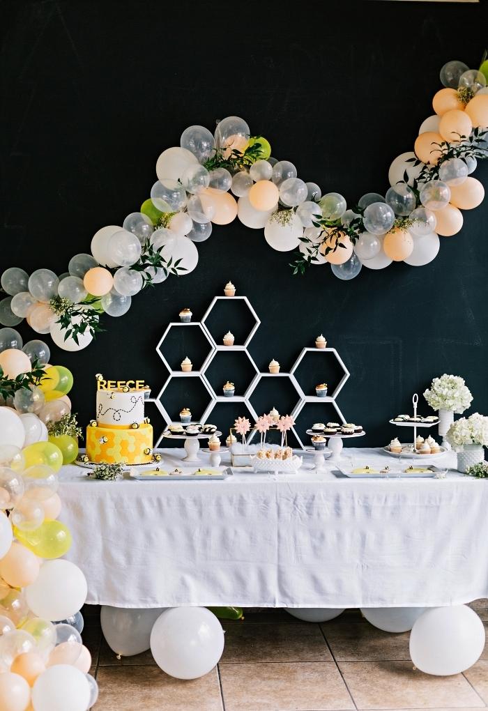 theme anniversaire abeilles en noir, jaune et blanc pour fêter le premier an de votre bébé, une déco de table d'anniversaire avec arche de ballons et de feuilles artificielle, buffet d'anniversaire avec bonbonnières et présentoir à cupcakes en forme de nid d'abeille décoré d'une arche de ballons sur un fond noir