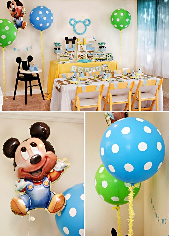 deco anniversaire enfant sur le thème mickey mouse en bleu, vert et jaune, décor de ballons mickey mouse et ballons pois, buffet gourmand thématique pour un anniversaire 1 an décoré de lettres en bois personnalisées