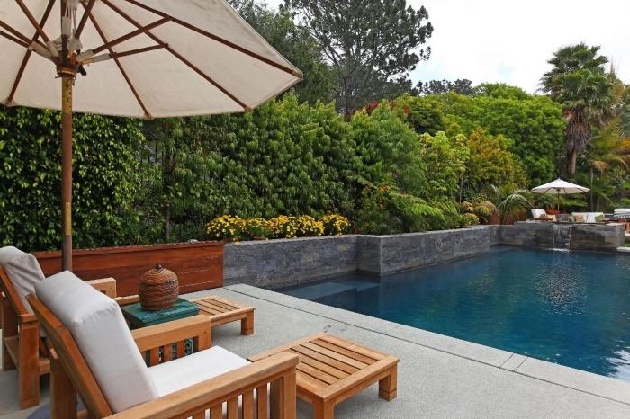 design extérieur piscine et terrasse, modèle de grande piscine avec cascade, meubles de piscine transats en bois