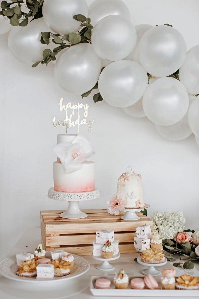 deco table anniversaire 1 an de style champêtre, arche de ballons blancs et de feuilles d'eucalyptus, candy bar d'anniversaire 1 an décoré de fleurs et de cage en bois