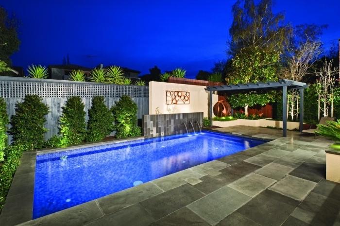 design extérieur contemporain avec piscine rectangulaire avec cascade, idée revêtement de terrasse en dalles