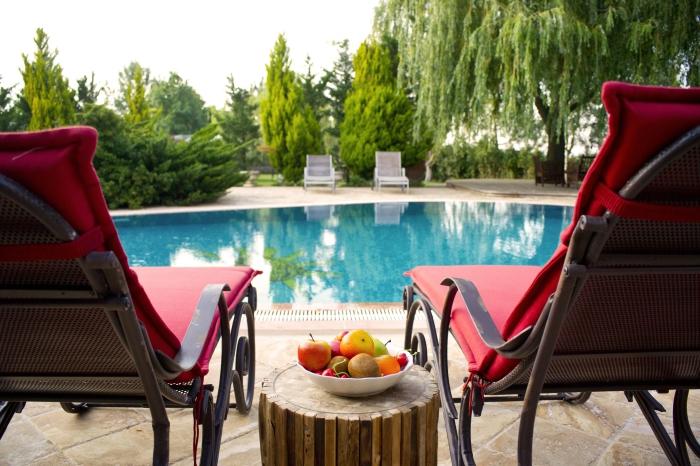 modèle de transat piscine en fer forgé avec housse rouge, deco piscine avec terrasse en dalles et meubles en fer