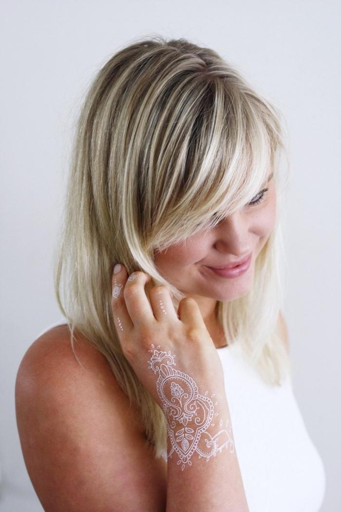 exemple de dessin henné en blanc sur la main à effet gants et bagues aux motifs dots et flèches, coupe de cheveux femme avec frange longue de côté