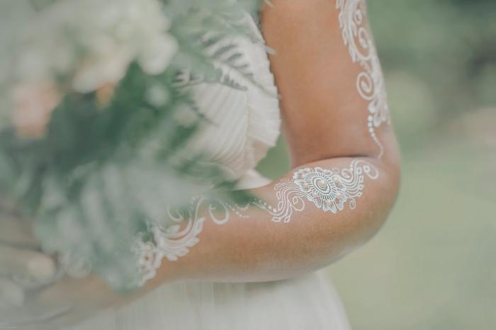 idée art corporel pour mariage, tattoo temporaire sur bras et mains aux motifs feuilles et fleurs avec paillettes