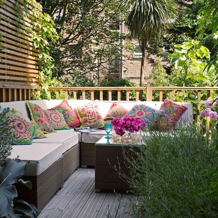 comment aménager son jardin, petit espace extérieur avec revêtement de sol en bois et meubles tressés foncés