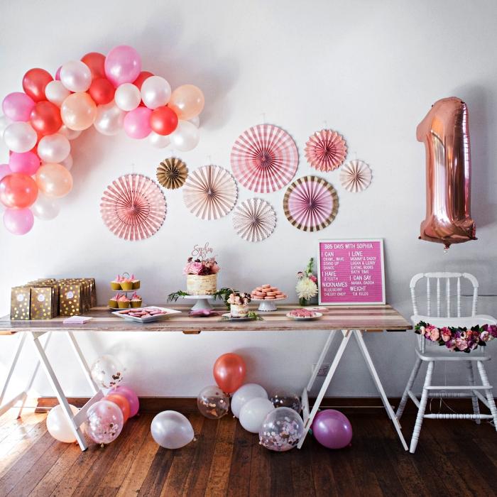 mur de rosaces en papier et arche de ballons pour la décoration de la sweet table gourmande, deco table anniversiare fille en camaïeu du rose
