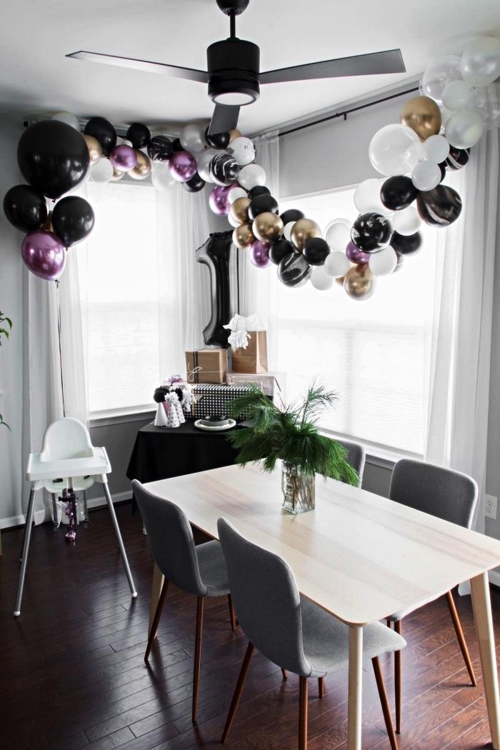 décoration anniversaire 1 de style minimaliste en noir et blanc avec une simple arche de ballons et un ballon chiffre