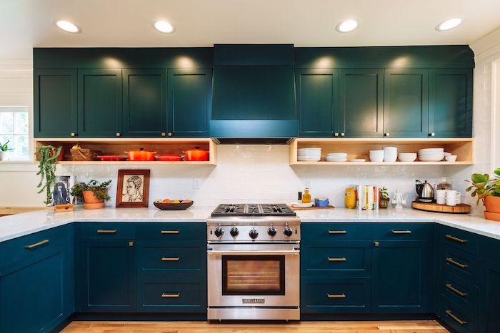 deco bleu petrole dans une cuisine en blei, blanc et orange avec plan de travail marbre blanc et étagères en bois pour ranger la vaisselle