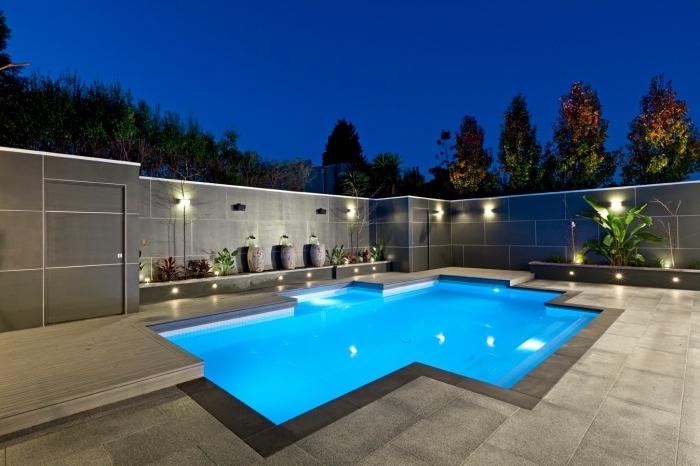 aménagement extérieur d'une maison moderne avec dalles gris anthracite et terrasse bétonnée autour d'une piscine