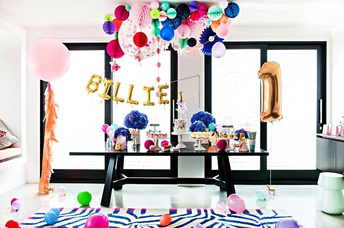 table d'anniversaire décorée d'une guirlande de ballons et de boules alvéolées, deco anniversaire enfant