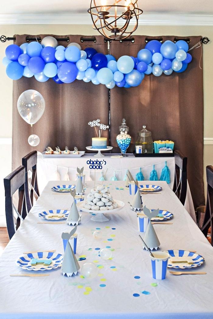 deco table anniversaire 1 an en bleu et blanc, centre de table confettis et set de table à rayures blanches et bleu, buffet d'anniversaire décoré d'une arche de ballons en nuances du bleu