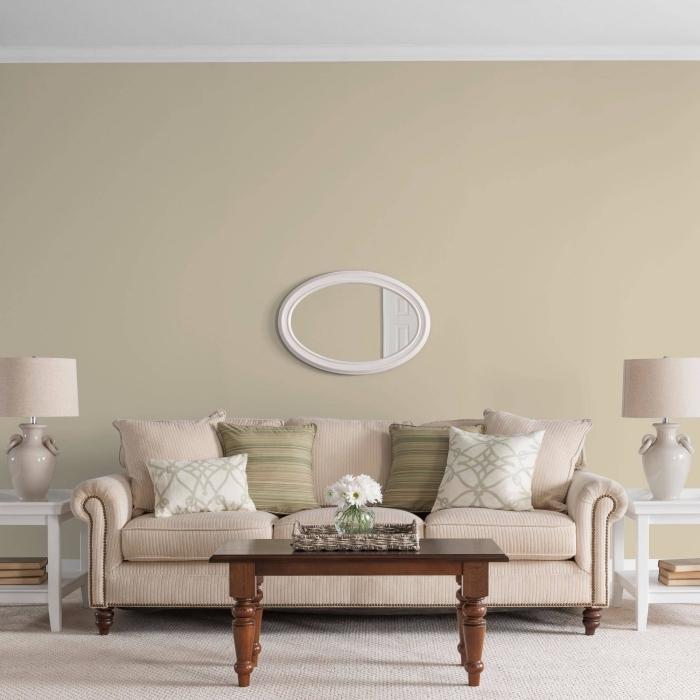 peinture beige dans un salon de style vintage aménagé avec meubles en bois blanc et marron foncé et accessoires en nuances pastel