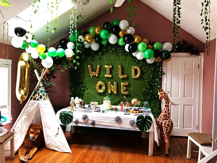 tipi indien, arche de ballons et toile de fond vert pour une decoration anniversaire garçon sur le thème de la jungle