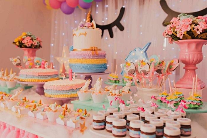 decoration anniversaire fille sur le thème licorne en tons pastel, déco de table anniversaire licorne ,décoration toile de fond en tulle, arche de ballons et cils de licorne pour un candy bar licorne