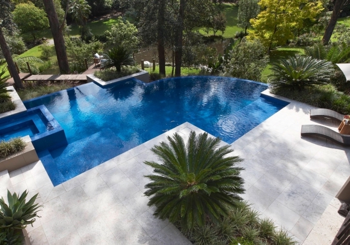 idée décoration autour d une piscine, exemple de terrasse de piscine bétonnée avec plantes vertes et transats