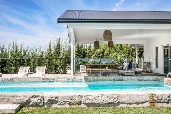idée amenagement terrasse piscine extérieure, modèle grande piscine en pierre avec plage de piscine bétonnée