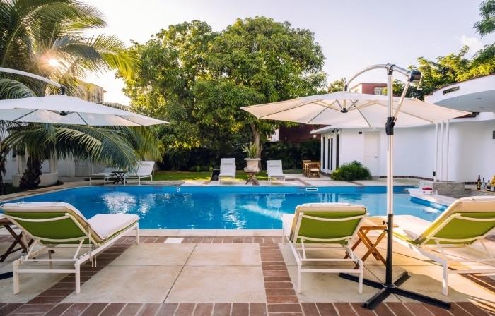 exemple d'amenagement terrasse piscine avec carrelage, modèle transat piscine avec matelas blanc et vert