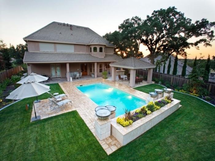 comment aménager une cour arrière avec piscine et jardin, idée gazon artificiel, exemple revêtement terrasse de piscine