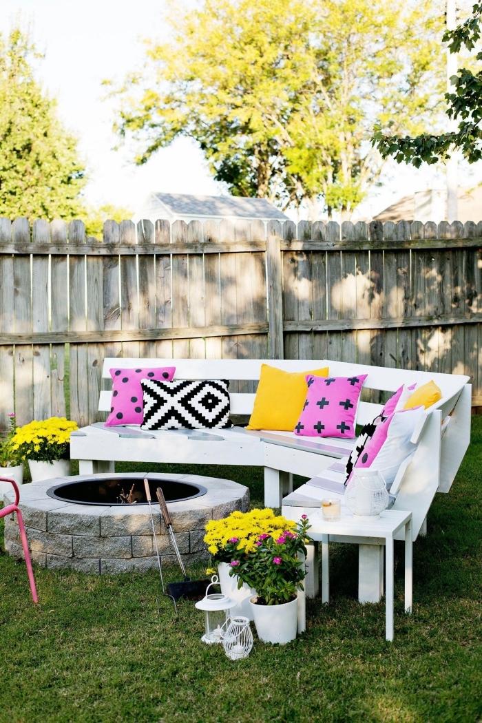 exemple comment aménager son jardin avec feu et banc en bois blanc sur pelouse, modèles de coussins décoratifs colorés