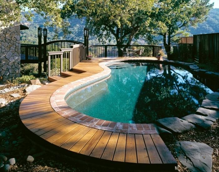 quelle forme pour une piscine, exemple plage de piscine en planches de bois clair, modèle piscine avec bordure pierre