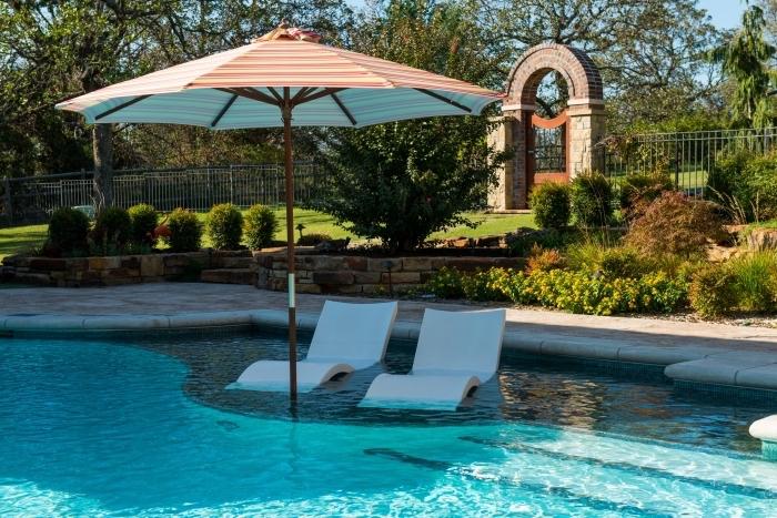 exemple d'amenagement terrasse piscine, modèle de piscine avec transats intégrés et parasol de piscine orange