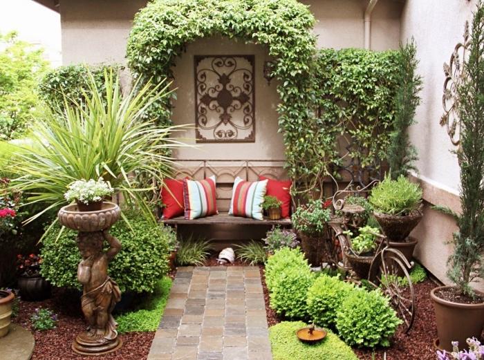exemple comment décorer un petit jardin avec allée en dalles et galets, petit banc en bois décoré avec coussins et arc vert