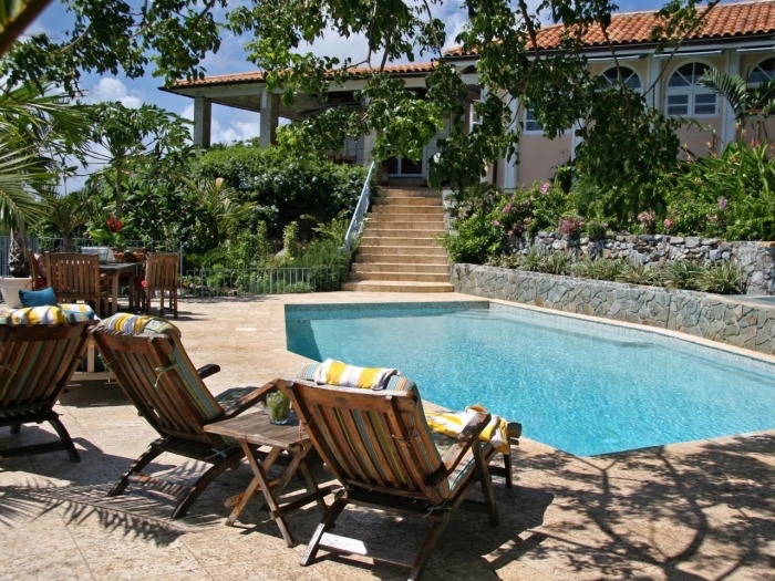 idée décoration cour arrière avec jardin et piscine, aménagement terrasse piscine avec transats en bois et matelas multicolore