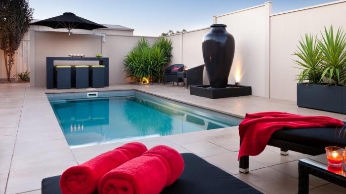 ambiance zen dans une cour arrière moderne aux clôtures blanches, décor cour arrière avec plage de piscine en béton