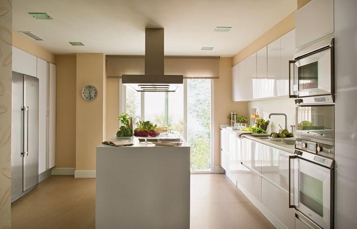 agencement cuisine avec îlot de style moderne, déco de pièce avec peinture sable, modèle cuisine en beige et blanc
