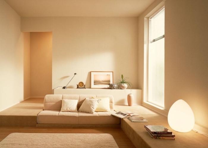 décoration monochrome dans une pièce lumineuse aux murs à peinture couleur sable claire avec grande fenêtre