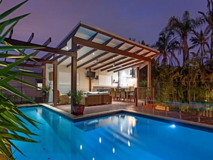 amenagement autour piscine photos, modèle de pergola avec cuisine d'été et salon de jardin tressé à côté d'une grande piscine