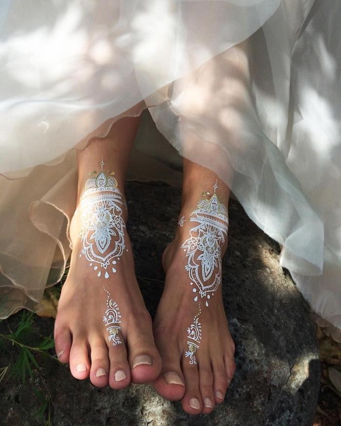 exemple de tatouage bohème sur pieds à effet, modèle de tattoo henné en blanc et argent aux motifs ethniques