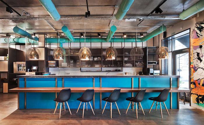 amenagement cuisine industrielle chic avec ilot central bleu, chaises scandianves noires, suspensions originales, sol en bois, étagères metalliques noires, tuyaux apparentes en bleu