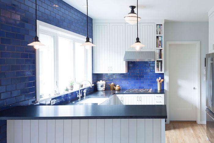 credence carrelage bleu marine, facade cuisine blanche vintage et plan de travail gris, suspensions originales, parquet bois clair