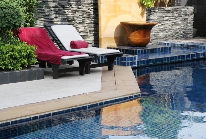 déco extérieure moderne d'esprit zen, exemple amenagement autour piscine avec transats noirs et serviettes colorées