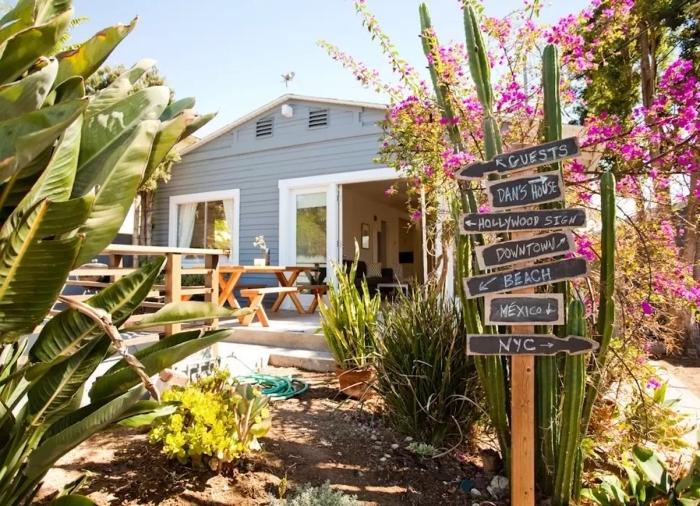 idée aménagement extérieur entrée maison, décoration petit jardin avec plantes vertes et meubles en bois clair