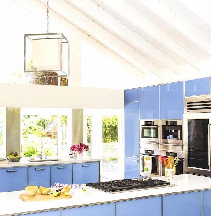 cuisine blanche aux accents bleu tirant vers le violet, elecotromenager inox, plans de travail blancs et une suspension originale