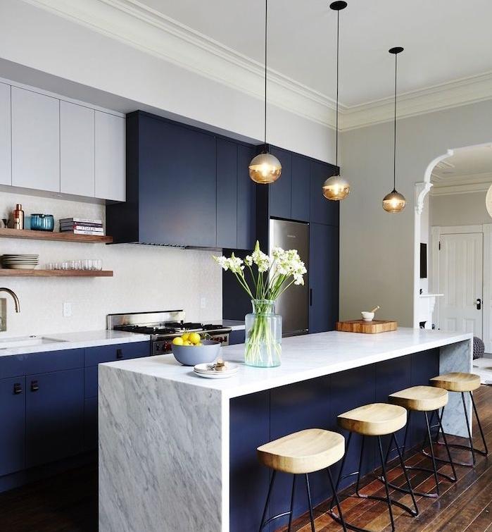 exemple cuisine bleu nuit avec plan de travail marbre sur un ilot en bleu foncé, tabourets de bar bois et metal, suspension industrielle, étagères bois