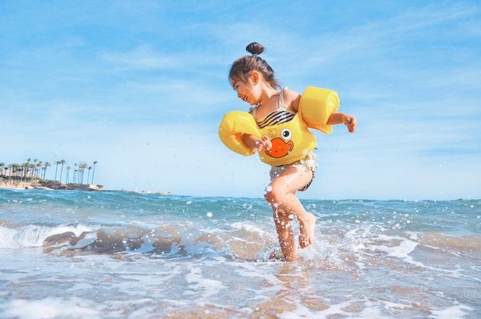 Fille au bord de la mer, idée comment s'amuser à la plage, enfant adorable, chignon haut, tuto coiffure facile, coiffure simple et rapide pour fille
