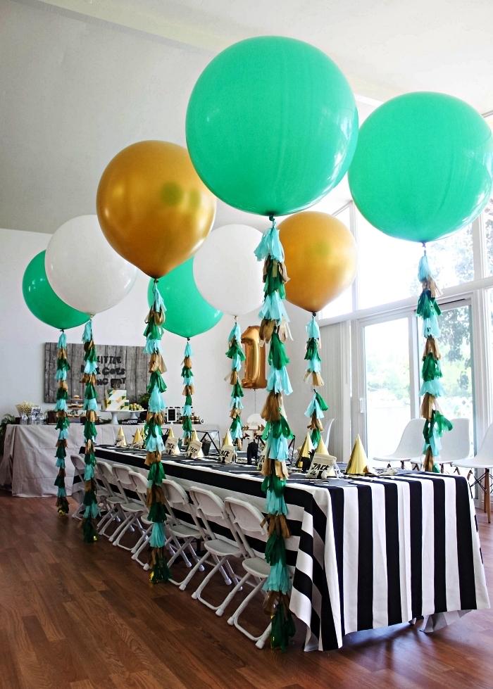 deco table anniversaire avec nappe à rayures noires et blanches, décor de ballons avec queues franges