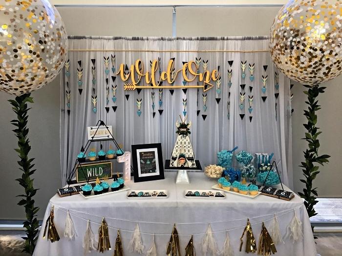 decoration anniversaire 1 an garçon sur le thème du far west, déco de table anniversaire avec ballons confettis à queue, des guirlandes à tassel et des bonbonnières en forme de tipi