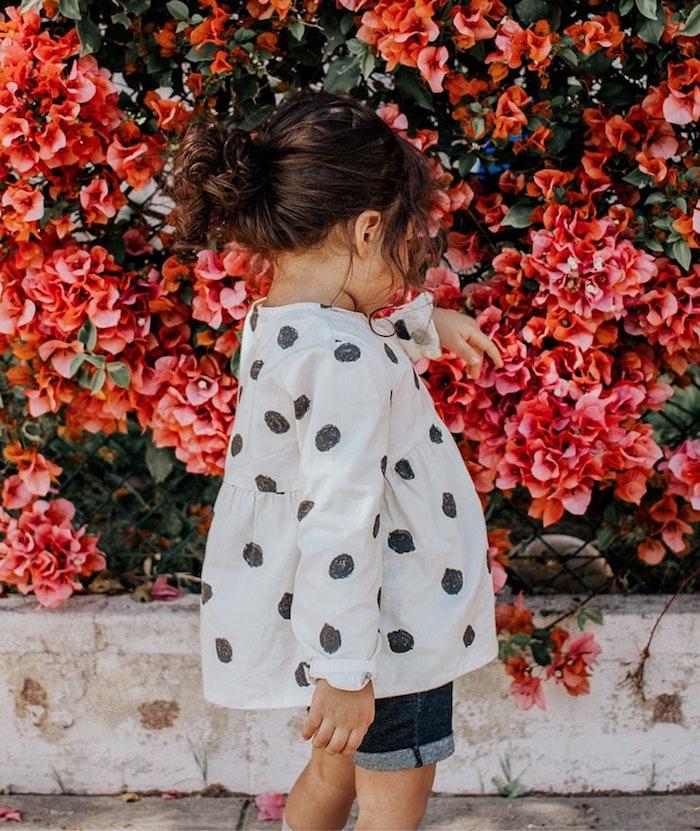 Adorable petite fille qui joue avec les fleurs dans la rue, coupe petite fille, coiffure facile a faire fillette cheveux