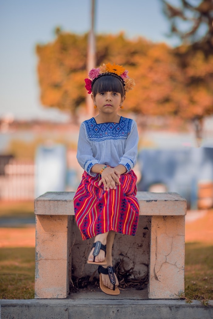 Photo inspirée par le style de Frida Khalo, jupe mexicaine, couronne de fleurs et chignon bas avec frange pour petite fille, tuto coiffure facile à faire