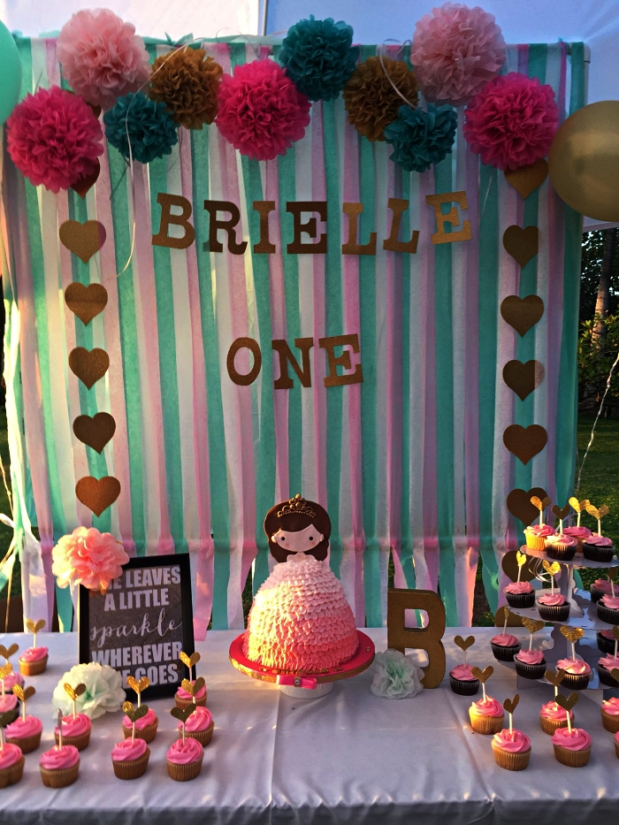 buffet gourmand sur le theme anniversaire princesse avec une déco de boules en papier de soie et rideau à franges en toile de fond