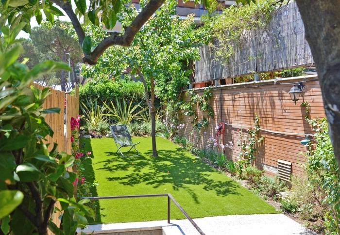 idee amenagement jardin avec clôture en bois, petite cour arrière avec pelouse artificielle et plantes grimantes