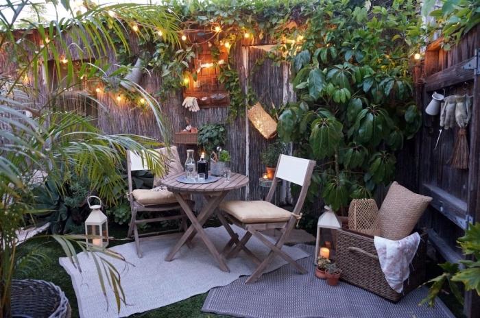 décoration jardin avec meubles en bois et guirlande lumineuse, idée aménagement terrasse et jardin photo avec clôture paille