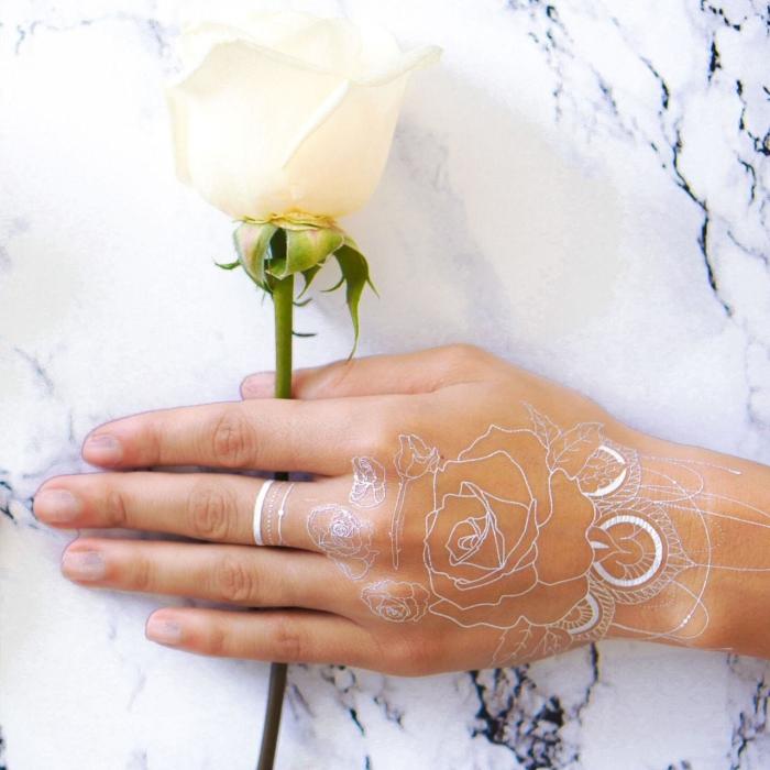 idée tatouage au henné sur main et doigts aux motifs floraux, petit tattoo temporaire sur le doigt à effet bijou