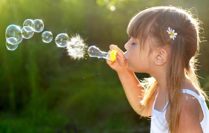 Ballons de savon, coiffure avec frange, coiffure enfant, coiffure petite fille mariage, belle fille stylée fleurs sur l'oreille