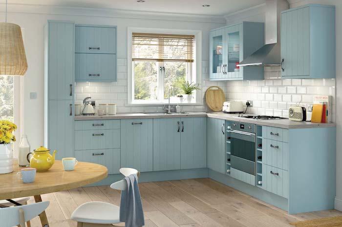 amenagement cuisine bleu pastel avec credence carrelage metro blanc, parquet bois clair, ouverture sur petit coin repas en chaises scandinaves et table ronde de bois